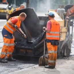 Oranzides tööriietes mehed tegemas teetöid Tallinna tänavatel